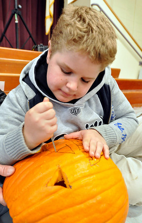 Middleton: Daniel Merrill, 8 carves a pumpkin to be displayed Saturday evening, during the annual pumpkin festival.   photo by Mark Teiwes / Salem News