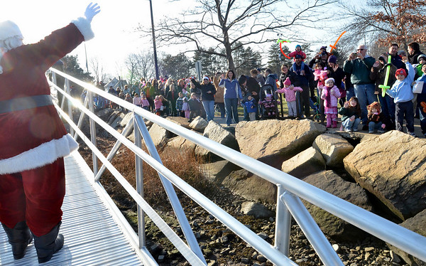 Danvers: A large crowd of families with eager children, greet Santa as he makes landfall. photo by Mark Teiwes / Salem News