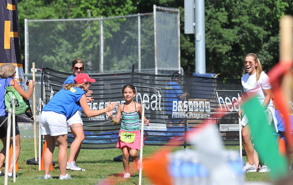 Hamilton: Abigail Williams of Beverly, 7, gets a high five from volunteers after competing the TriROK Foundation's kids's triathlon at Patton Park.    photo by Mark Teiwes / Salem News