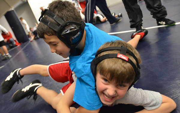 Danvers: 7-year-old Kolby Berube of Salem, left, and Alby Lavita of Topsfield, 6, wrestle at the North Shore Youth Wrestling clinic.    photo by Mark Teiwes / Salem News