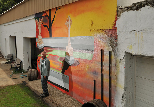 Salem:  City of Salem work Richard Martineau stands in front a mural he painted on a maintenance building in Greenlawn Cemetery.   photo by Mark Teiwes / Salem News