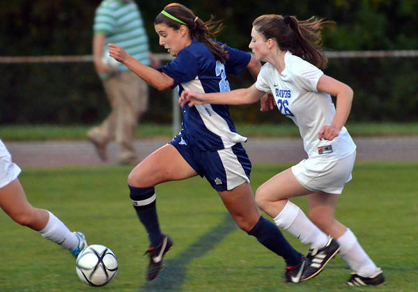 Danvers:  Peabody's  Haley Dowd, left, runs past Danvers defender 26 on her way to the goal.  photo by Mark Teiwes / Salem News