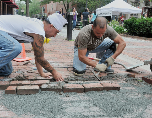 Salem: PJ Marchant, left, and Tony Correia replace and level parts of the brick sidewalk on Essex Street to mitigate tripping hazards.  photo by Mark Teiwes / Salem News