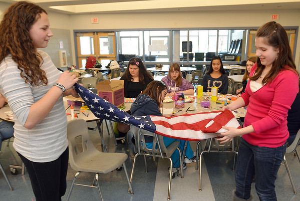Danvers: Girl Scouts Julia Mini, 13, left, and Rebecca Hardenstine, 13, of Danvers Troop 843 fold a flag from SFC David Richey, who is stationed in Afghanistan. Before he was deployed, he was given a box of Girl Scout Lemonades cookies with a heart on it and the name and address with Troop 843 on it. The soldier kept the heart in his wallet, and to pay them back, sent them a flag that has flown over Camp Alamo on Veterans Day 2010.  photo by Mark Teiwes / Salem News