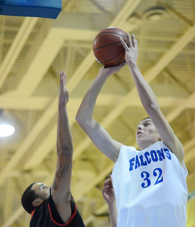 Danvers: Danvers center George Merry puts up a shot defended by Salem's Antonio Reyes. photo by Mark Teiwes  / Salem News