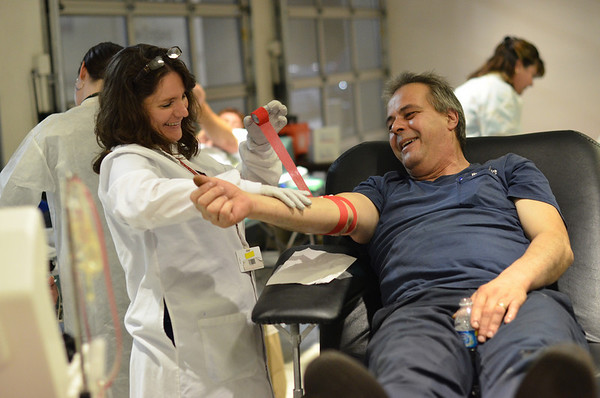 Danvers:  Tracy Beaudette, collection specialist, finishes a bandage after Bill McElveen, Honda North technician, donated at a Red Cross blood drive.  photo by Mark Teiwes / Salem News