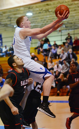 Danvers: Danvers captain Sean Mahegan flys into the paint through Salem's Antonio Reyes for a layup.  photo by Mark Teiwes  / Salem News
