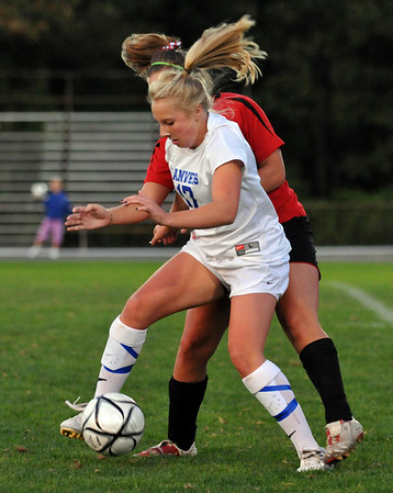 Danvers:  Danvers High School girls soccer player Corey Persson shields the ball from a Salem defender.  photo by Mark Teiwes / Salem News
