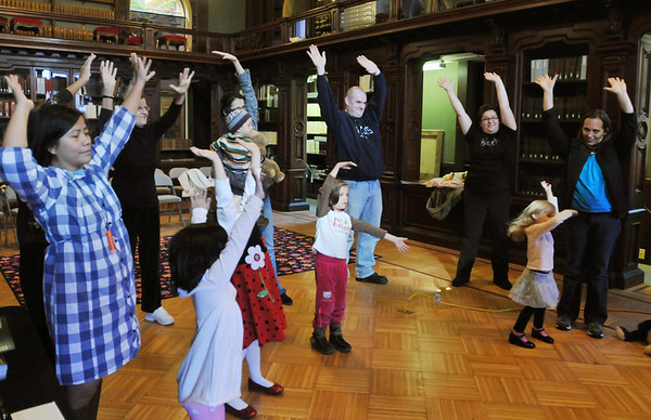 Peabody: Families practice ballet positions together at the library.   photo by Mark Teiwes / Salem News