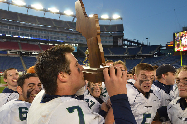 Foxborough: Pingree quarterback Brendan Oliver kisses the Norm Walker Bowl trophy after the triumph over Rivers. photo by Mark Teiwes / Salem News