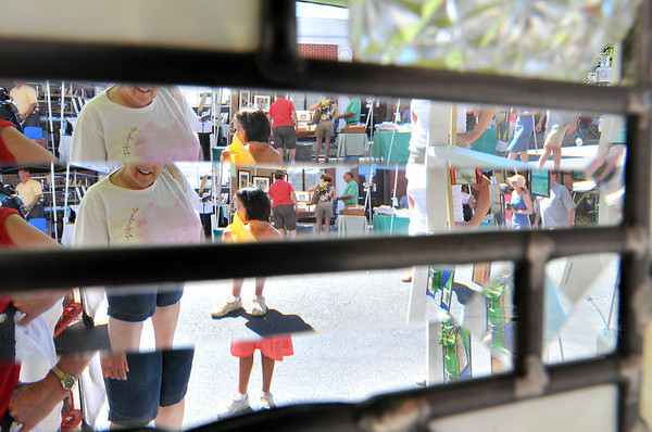Beverly:  Festival attendees are seen through a prism part of a window by stained glass artist Kristine Arnold at Arts Fest Beverly.  photo by Mark Teiwes / Salem News