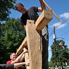 Ipswich: Jim Whidden, master woodworker and housewright, uses a wooden sledgehammer to pound a post of the timber frame house into place.  Jordan Swenton of Allston helps to steady the structure. photo by Mark Teiwes / Salem News