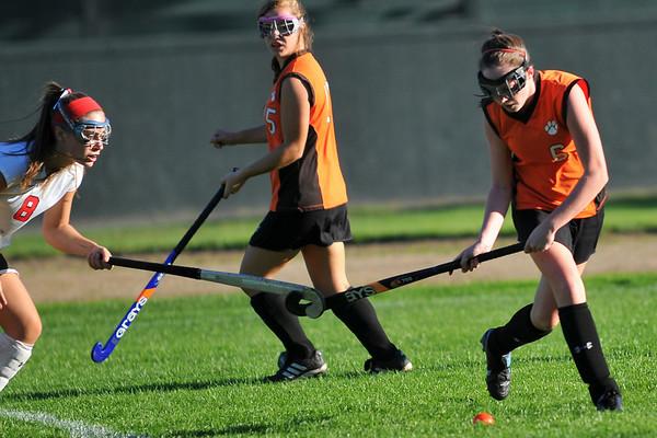 Marblehead's Lindsay Franklin, left, hooks sticks with Beverly's Brooke Malloy. photo by Mark Teiwes / Salem News