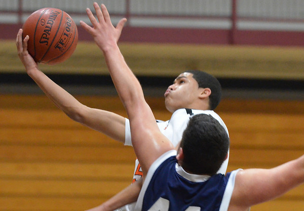 Wenham: Beverly's Aven Jones drives to the hoop defended by Peabody's Fotakis Sotiri.  photo by Mark Teiwes  / Salem News