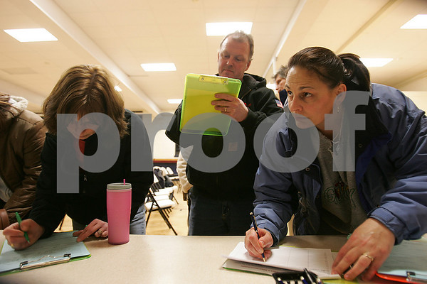 Peabody: Joyce Trott from Lynn, right, adds her information to a petition as her husband, Mike Trott, center, and Carleen Sobezenski of Salem, left, fill out other forms before a meeting at St. Thomas Church in Peabody to brainstorm ways to save St. Joseph's School in Salem from closing on Wednesday night. The Trott's have three children, a second grader, a seventh grader, and an eigth grader, in the St. Joseph's School system. Sobezenski has an eigth grader that will be graduating at the end of the spring, but is more concerned about where her 2-year-old will go to school. The Archdiocese, which owns the school, announced its closing this month. Photo by Matt Viglianti/Salem News Wednesday, January 21, 2009