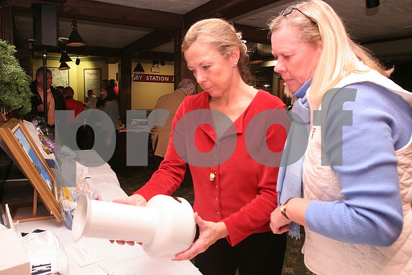 Salem: Noreen Casey, left, and Malia Griffin examine a vase they intend to bid on during the silent auction at the 15th annual Salem Children's Charity Fundraiser on Tuesday. Photo by Matt Viglianti/Salem News Tuesday, December 16, 2008