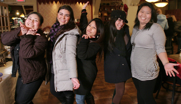 Saugus: From left to right, Chavanuan Jitjaroonsri from Thailand, Camila Silva from Brazil, Suphawadee Dontriros from Thailand, Luisa Sanchez from Nicaragua, and Yui Sriwan pose at a holiday party for local au pairs at Prince Pizza in Saugus on Wednesday night. About 40 au pairs from around the world attended the celebration. Photo by Matthew Viglianti/Staff Photographer Wednesday, December 16, 2009.