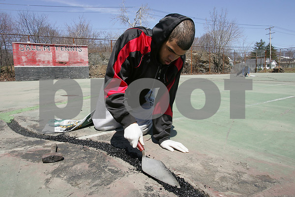 Salem: Juan Carrasco, a senior captain on the Salem High School tennis team, prepares a crack in the school's tennis court to be patched while volunteering his time to help repair the court on Sunday afternoon. Although the tennis season has already started at Salem High, the disrepair of the courts have forced the boys and girls teams to practice at Salem Willows and Salem State. Carrasco hopes the court will be ready for play for the girl's next home match on Wednesday. Photo by Matthew Viglianti/Staff Photographer Sunday, April 19, 2009.