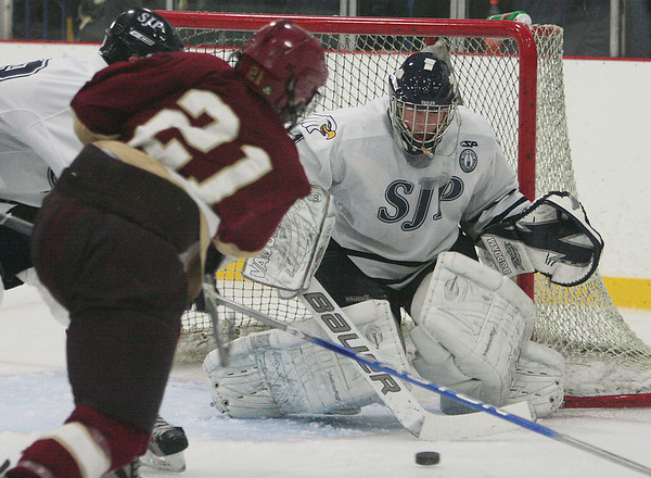 Wilmington: St. John's Prep sophomore goalie David Letarte turns away a shot from BC High senior assistant captain Collin Norton (21) during the third period of the Prep's game against BC High in Wilmington on Saturday. The Prep won the game 3-2. Photo by Matthew Viglianti/Staff Photographer Saturday, January 23, 2010.
