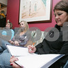 Swampscott: Donna Rousseau from Marblehead, right, jots down notes as Susan Purchase from Marblehead, center, and Elaine Murphy from Swampscott listen during a SHE Network board meeting at the home of Sonja Groundstra in Swampscott on Wednesday. Photo by Matt Viglianti/Salem News Wednesday, November 05, 2008