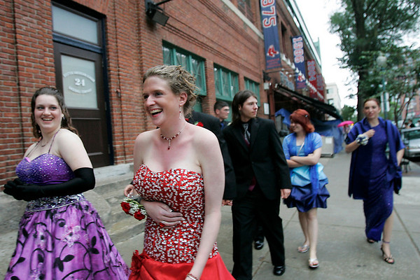 Boston: Sarah Willey, second from left, and Jessica Jollotta, far left, lead a group of their friends up Yawkee Way outside Fenway Park in Boston after arriving early for the Beverly High School prom on Thursday evening. The dance was held at the State Street Pavillion Club, which overlooks the Park's playing field from behind home plate. Willey and Jollotta are both seniors at Beverly High School. Photo by Matthew Viglianti/Staff Photographer Thursday, June 10, 2010.