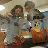 Salem: Gillianne Pagan, left, and Alicia Grenier, both 9-year-old third grade students at the Carlton School in Salem, peer through a glass case at artwork created by Salem High School students during the Salem Public Schools Arts in the Evening show at Salem High School on Wednesday. Art created by students from Salem schools grades K-12, featuring paintings, drawings, photographs, sculptures, and graphic designs, was on display, and concert performances were also held in the field house. Photo by Matthew Viglianti/Staff Photographer Wednesday, May 6, 2009.