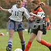 Peabody: Nicolle Simon from the U-12 Peabody Miracles, left, crosses the ball just ahead of a tackle from Alice Hurst-MacDonald from the U-12 Ipswich Strikers during the second half of their teams' semi-final match-up in the 18th annual Peabody Youth Soccer Columbus Day Tournament on Monday. Peabody won the game 2-0 to advance to the final. Photo by Matt Viglianti/Salem News Monday, October 13, 2008