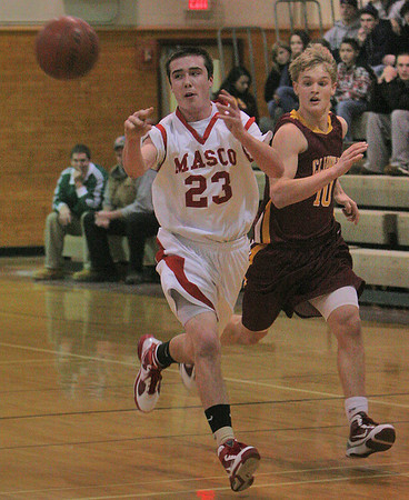 Topsfield: Collin Burke, a senior forward for the Masconomet Chieftains, distributes the ball on a fast break as Newburyport's Kyle Vhlisi sprints to keep pace during their teams' game in Topsfield on Thursday. Photo by Matthew Viglianti/Staff Photographer Thursday, January 7, 2009.
