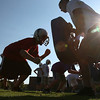 Danvers: Drew Salvo from Danvers, 13, left, explodes into a blocking bag held by Danvers High School football player Zach Ryan, who is entering this season as a senior captain at tight end and definsive lineman, right, during a drill at a youth football skills clinic at Danvers High School on Tuesday. Photo by Matthew Viglianti/Staff Photographer Tuesday, July 27, 2010.