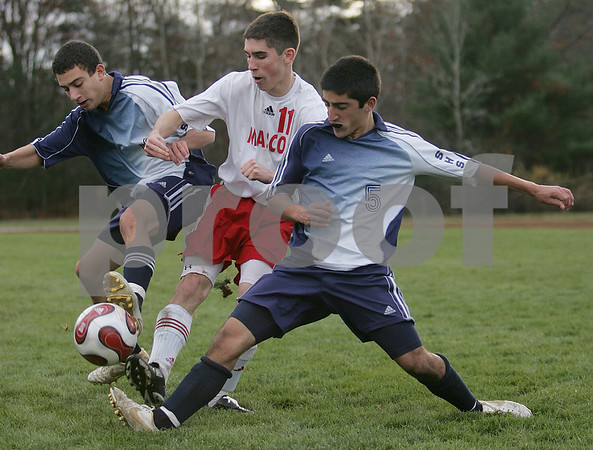 Topsfield: Masconomet senior Mark Evans (11) fights to keep possession through challenges by Swampscott senior captain Matt Gateman, left, and junior Kyle Taylor during the second half of Masconomet's 2-0 win over the Big Blue in their Division 2 North quarterfinal game in Topsfield on Tuesday. Photo by Matt Viglianti/Salem News Tuesday, November 11, 2008