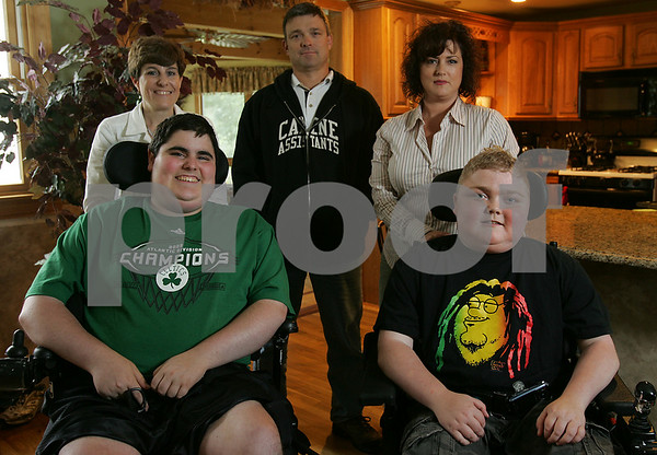 Beverly: Lauren Ferrari of Danvers and her son Nick Larkin, 17, left, pose with Paul and Natalie Guadenzi and their son Max, 14, in the Guadenzi's home in Beverly on Tuesday afternoon. Nick and Max suffer from muscular dystrophy, and at the last minute, a summer camp they attend was cancelled by the Muscular Dystrophy Association, which funds the camp, because of fears of swine flu. Now, the families of children hoping to attend the camp must raise $675 per family in order to go. Photo by Matthew Viglianti/Staff Photographer Tuesday, June 23, 2009.