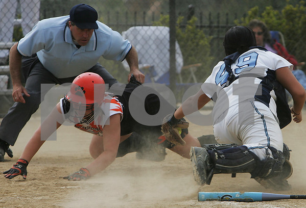 Beverly: Ipswich junior Kelley Michael dives safely into home ahead of a tag attempt by Peabody junior catcher Morgan Yeo to score on a hit by senior captain Kerry Desmond during the bottom of the seventh inning of the Courtney Marie Corning Memorial Softball Tournament championship game at Endicott College in Beverly on Sunday afternoon. Ipswich scored four runs after entering the seventh inning down 10-2, but fell short despite a two-out rally, and lost 10-6. Peabody won the game to defend its 2008 tournament championship. Photo by Matthew Viglianti/Staff Photographer Sunday, May 24, 2009.