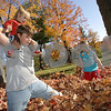 Danvers. Collin Butler, 12, from Danvers gives his brother Brody Kennison, 1, a piggy-back ride through a leaf pile as their sister Jennalynn Kennison, 7, plays nearby outside the Peabody Institute Library in Danvers. Photo by Matthew Viglianti/Salem News Monday, October 20, 2008.