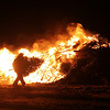 Salem: John White with the Department of Public Services in Salem adds a tree to the fire at the annual Christmas tree bonfire at Deadhorse Beach in Salem on Wednesday night. An estimated 2500 trees were burned in this year's fire. Photo by Matthew Viglianti/Staff Photographer Wednesday January 6, 2010.