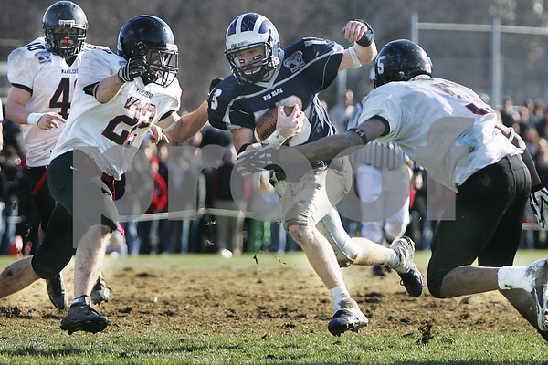 Swampscott: Swampscott junior captain Chris Cameron tries to cut through Marblehead tacklers, senior captain Dan Comeau, left, and junior Taariq Allen, right, during the first half of the Big Blue's 21-13 win over their neighboring rival for the Northeastern Conference Small championship on Thursday afternoon in Swampscott. The game marked the 100th meeting between the two teams. Photo by Matthew Viglianti/Staff Photographer Thursday, November 27, 2008.