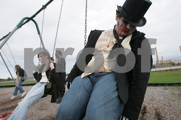 Salem: Tom Bush of Beverly acts like a zombie on the swings at Collins Cove while waiting with his friends for the start of the Zombie Walk through Salem on Sunday. Photo by Matt Viglianti/Salem News Sunday, October 05, 2008