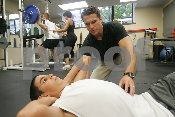 """Beverly: Dr. Michael Stare, director of Spectrum Fitness Consulting in Beverly, encourages Nick George, 13, from Peabody to maintain good form during a set of thoracic mobilization exercises as Michelle Theriault, a holistic nutritionist and trainer, spots Jed Dickman of Beverly during a set of barbell squats during a training session on Tuesday. Clients visit Spectrum Fitness Consulting to rehab from injuries or to improve their health and athletic performance. Both Dr. Stare and Theriault will be speaking at an upcoming seminar """"How to Finally Take Care of Your Health and Fitness"""" in the Cummings Center on September 16. Photo by Matt Viglianti/Salem News Tuesday, September 09, 2008"""