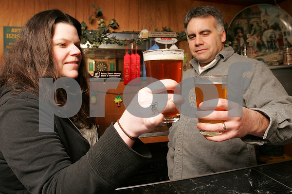 Hamilton: Danielle Broderick and her husband, Tim, examine the color and clarity of a beer crafted by a local brewery, left, as well as a Czech pilsner they brewed together this winter, in their basement bar at their Hamilton home on Tuesday. The couple have been brewing beer for over 10 years, and enjoy sharing tips with other local brewers, as well as new-comers to homebrewing. Photo by Matthew Viglianti/Staff Photographer Tuesday, March 10, 2009.