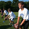 Danvers: From right to left, Ryan Chasse, 14, Josh Koen, 13, Brian McKinnon, 13, and Bobby Kobierski, 12, practice their footwork during quarterback drills at a youth football clinic run by the staff of the Danvers High School football team on Tuesday afternoon. Photo by Matthew Viglianti/Staff Photographer Tuesday, July 27, 2010.