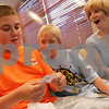 Salem: Brothers Ryan, 14, left, and Derek, 9, DuBois and their mother, Angela, react with surprise while reading an accurate prediction made by magician Evan Buso-Jarnis at the start of a magic trick during his show at the Salem Waterfront Hotel & Suites in Salem on Wednesday. Photo by Matt Viglianti/Salem News Wednesday, August 06, 2008