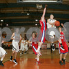 Beverly: Beverly junior guard Nate Knudson hangs in the air while attempting a reverse lay-up as Burlington senior captain Matt Trahan, center, leaps to block the shot during the third quarter of the teams' state tournament game in Beverly on Thursday. Photo by Matthew Viglianti/Staff Photographer Thursday, February 26, 2009.