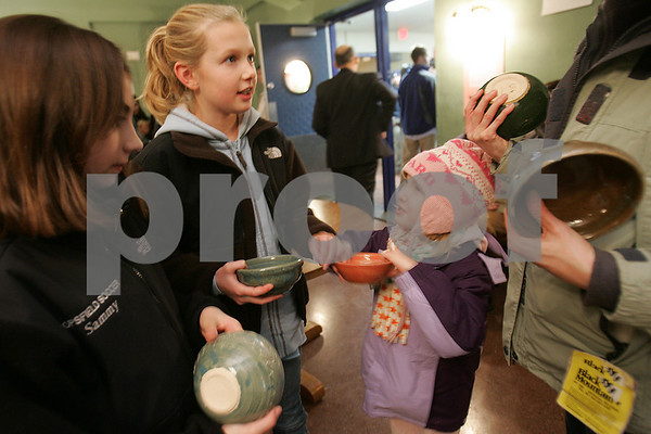 Danvers: Lindsey Byman, 5, from Topsfield, center right, attempts to get the attention of her older sister, Laura, 10, to show Laura her favorite bowl as Laura speaks with their mother, Lori, right, and family friend Sammy Dindo, 10, from Topsfield looks on at the 10th annual Empty Bowls Dinner Party at the Prep on Thursday. Over 400 bowls made by Prep students were on sale as part of the fundraiser, which raises money for Haven from Hunger in Peabody. Photo by Matt Viglianti/Salem News Thursday, January 15, 2009