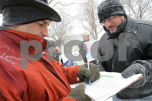 Salem: Daniel Albert from Marblehead, left, signs up to receive information from HealthLink as Charlie Harak from Melrose holds the clipboard for him during a protest held by HeathLink outside Salem Power Station on Sunday. Photo by Matthew Viglianti/Staff Photographer Sunday, March 1, 2009.