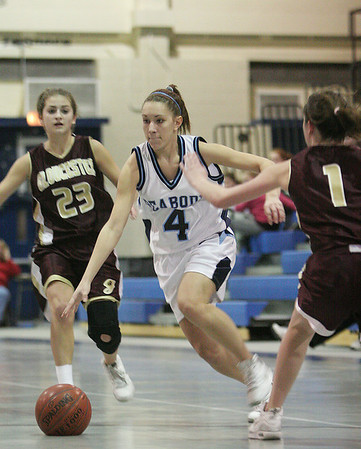 Peabody: Peabody senior captain Carissa Milley, center, dribbles through a pair of Gloucester defenders during their teams' game at the Peabody High School field house on Thursday night. Photo by Matthew Viglianti/Staff Photographer Thursday, January 28, 2010.