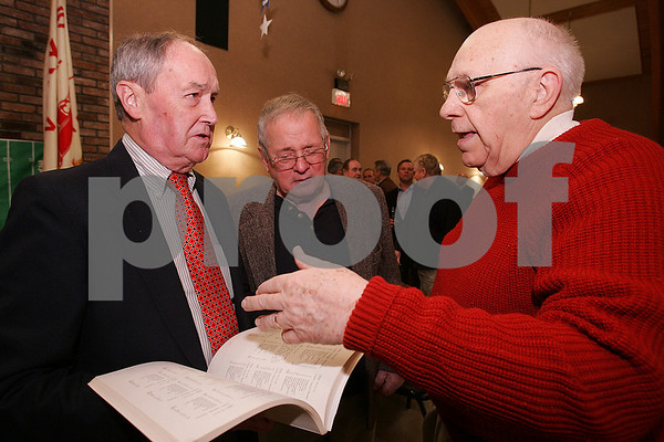 "Marblehead: Former Marblehead football players, from left, Dick Farrell, class of 1950, Bill Gillis, class of 1955, and Parker Caswell, class of 1950, talk while leafing through a book titled ""75 Years of Marblehead Football"" by former Marblehead High School teacher Bill Peabody, during ""Old Timers Night"" at the Gerry 5 Social Club in Marblehead on Monday. Players from past Marblehead and Swampscott football teams gathered there to celebrate their inter-town football rivalry, and to gear up for the 100th meeting of the teams this Thanksgiving Day. Photo by Matthew Viglianti/Staff Photographer Monday, November 24, 2008."