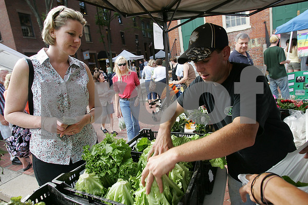 "Salem: Angie Kruse from Salem buys red leaf and Boston lettuce from Jeff Simone of Simone Farms in Methuen at the debut of the weekly Salem Farmers Market in Derby Square on Thursday. ""We try to buy everything we can in Salem,"" said Kruse. ""It's nice to buy local."" Photo by Matthew Viglianti/Staff Photographer Thursday, June 25, 2009."