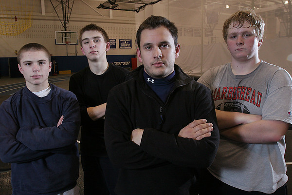 Swampscott: Mike Stamison, head coach of the Marblehead/Swampscott wrestling team, center right, poses with his captains, from left, Josh Levy, Kristian Kotov, and Jon Taylor, at practice on Thursday. Photo by Matthew Viglianti/Staff Photographer Thursday, January 7, 2010.