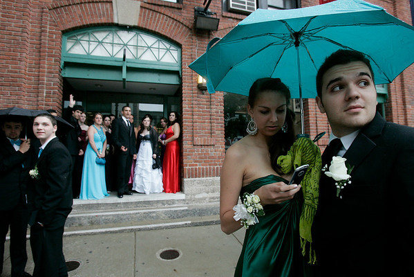 Boston: Taylor Rapalyea checks her messages as Jack Begaj watches an arriving limousine while taking shelter from the rain underneath an umbrealla outside the State Street Pavillion Club at Fenway Park, where the Beverly High School prom was held on Thursday. Photo by Matthew Viglianti/Staff Photographer Thursday, June 10, 2010.