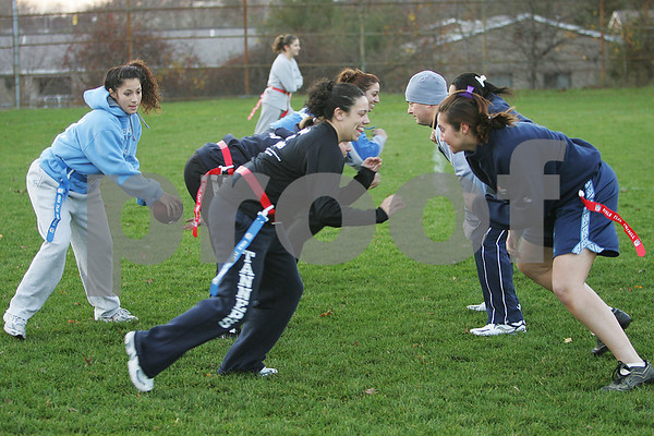 Peabody: Kenia McKeon handles the snap as the line prepares to block during a Powder Puff football practice at Peabody High School on Monday. The team plays its first ever game on Saturday against Revere. Photo by Matthew Viglianti/Staff Photographer Monday, November 17, 2008.