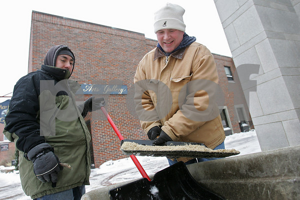 Salem: Jose Sandoval of Lynn, left, and Bob Naylor of Beverly use shovels to carry sand to spread on Salem sidewalks during a snowstorm on Monday afternoon. The men work for a Salem landscaping company that contracted to clear the area around the former armory building, and began working at 5 a.m.. Photo by Matthew Viglianti/Staff Photographer March, 2, 2009.